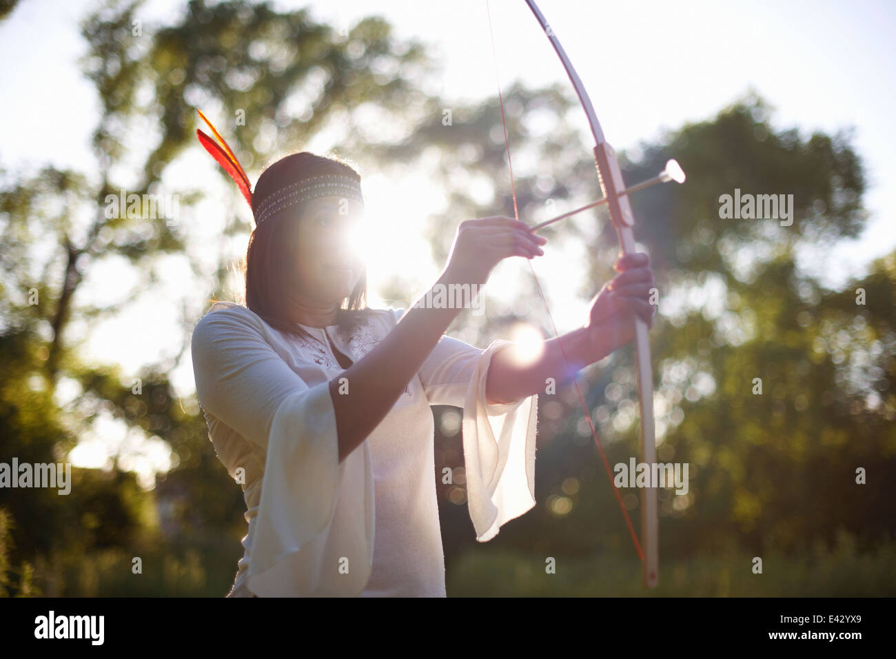 Mature woman in woodlands aiming bow and arrow - Stock Image