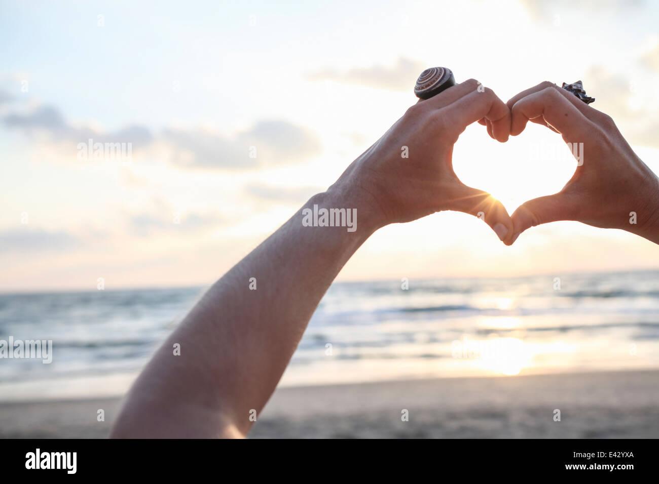 Female hands making heart shape at sunset on beach - Stock Image