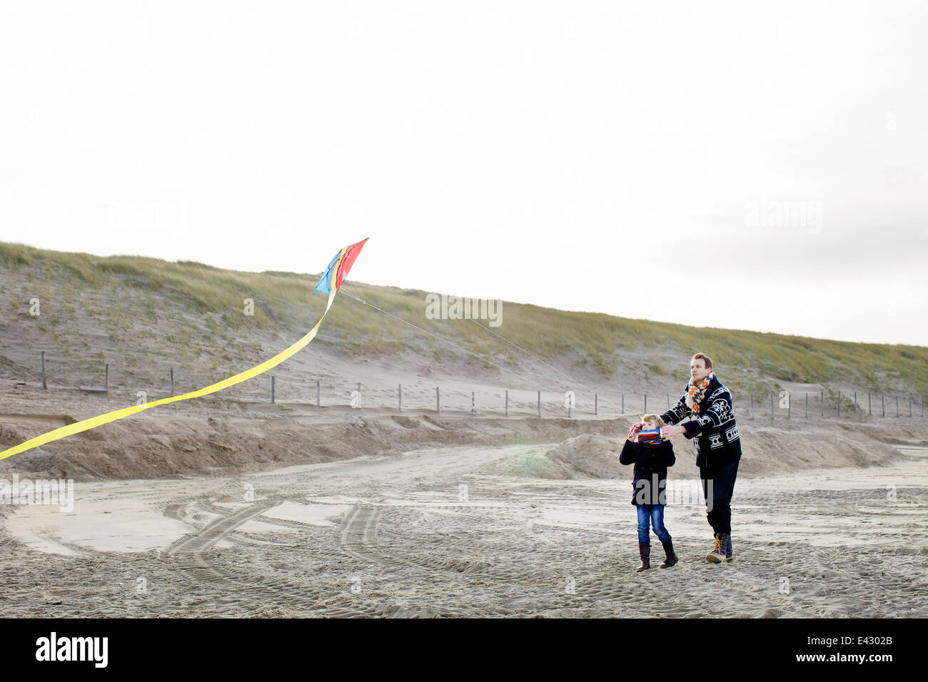 Mid adult man and son flying kite on beach, Bloemendaal aan Zee, Netherlands - Stock Image