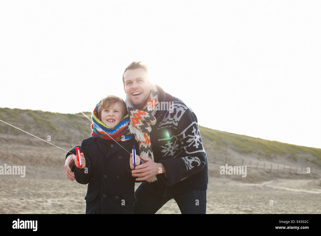 Mid adult man flying kite with son on beach, Bloemendaal aan Zee, Netherlands - Stock Image
