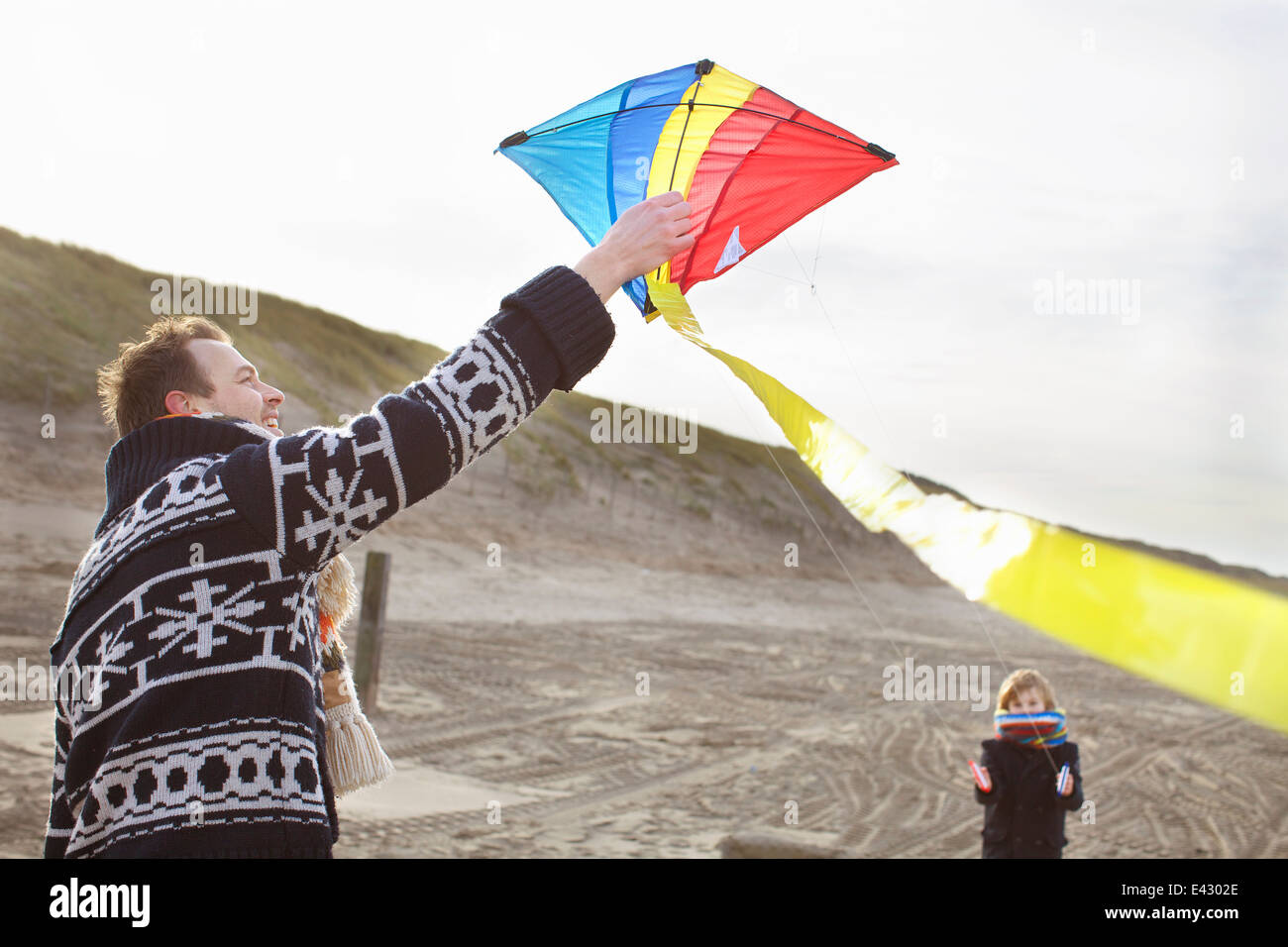 Mid adult man and son preparing to fly kite on beach, Bloemendaal aan Zee, Netherlands - Stock Image