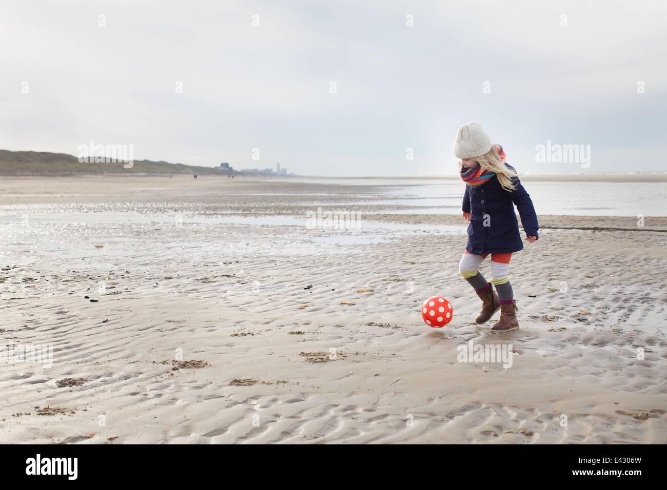 Three year old girl playing football on beach, Bloemendaal aan Zee, Netherlands Stock Photo