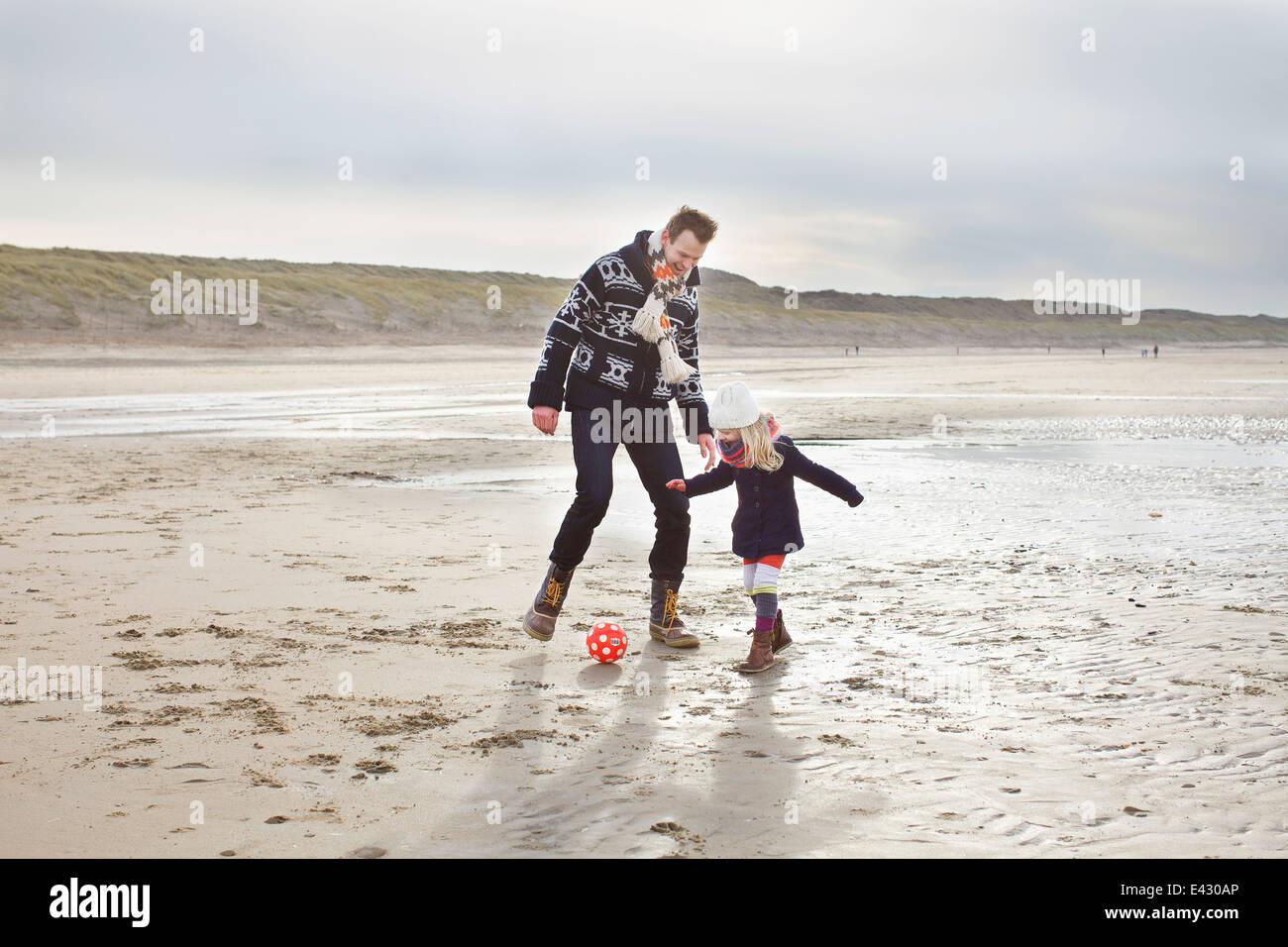 Mid adult man with daughter playing football on beach, Bloemendaal aan Zee, Netherlands - Stock Image