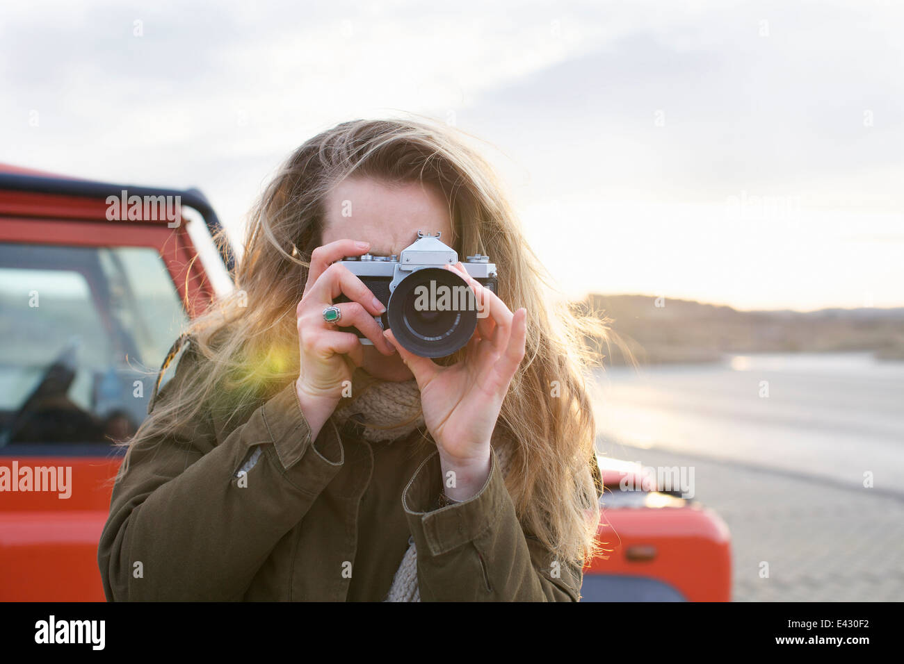 Mid adult woman photographing with SLR in coastal parking lot - Stock Image
