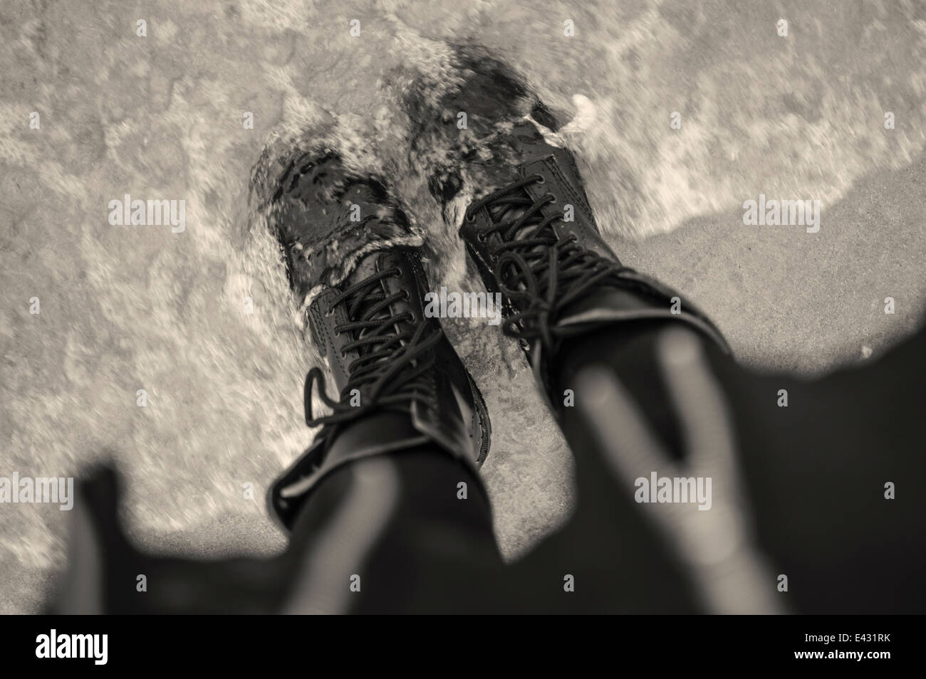 High angle view of young woman in laced boots in sea - Stock Image