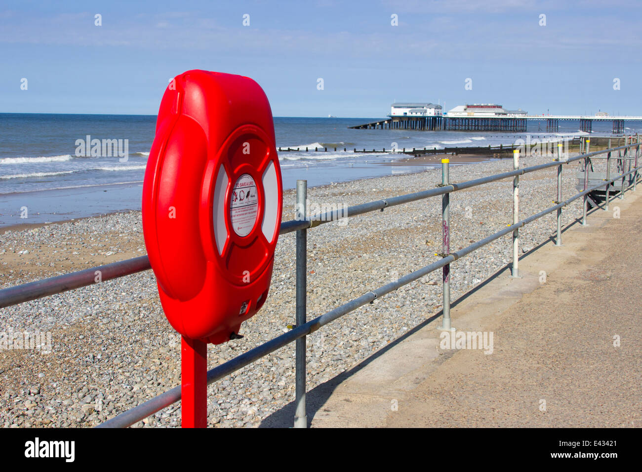Lifebelt on the seafront at Cromer, Norfolk. Pier and lifeboat station in background. - Stock Image