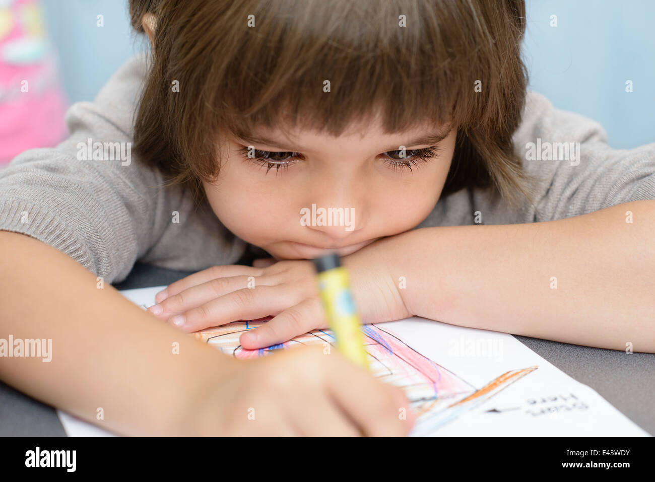 Lonely Girl drawing at kindergarten - Stock Image