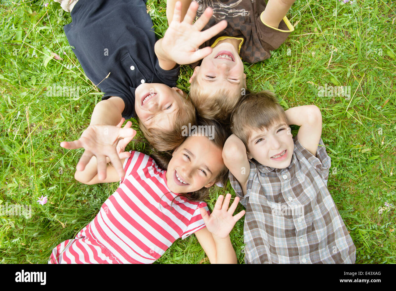 For happy kids on grass in summer day - Stock Image