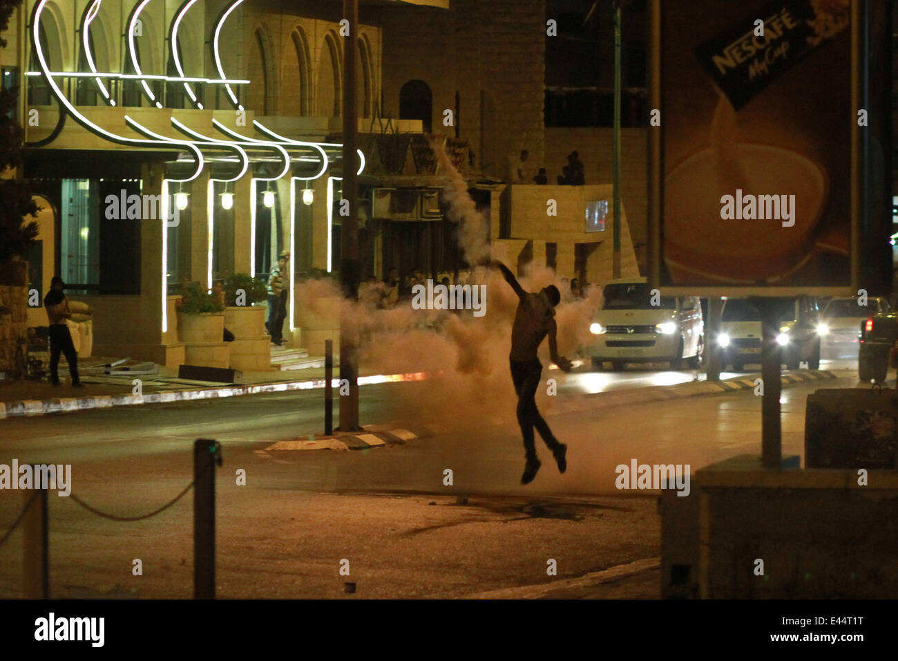 Bethlehem. 2nd July, 2014. A Palestinian protester throws stones at Israeli soldiers during clashes near Rachel's - Stock Image