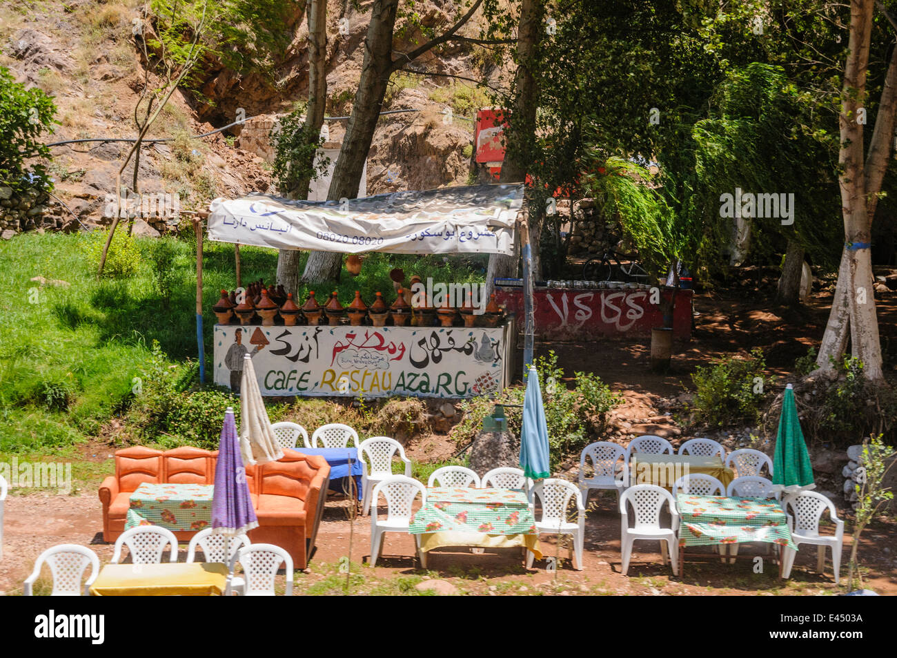 Plastic patio tables, chairs with parasols at restaurants on the banks of the Ourika River, Ourika Valley, Atlas - Stock Image
