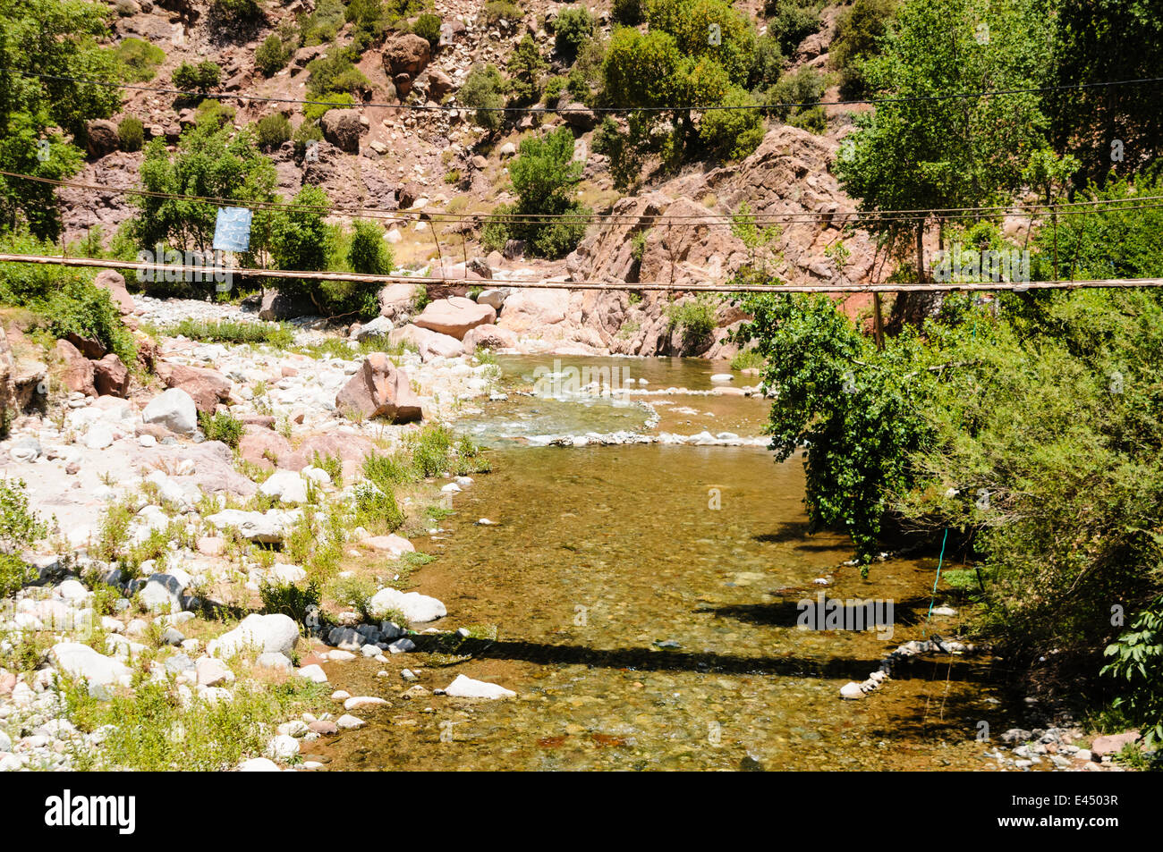 A potentially dangerous rickety bridge over the Ourika River, Ourika Valley, Atlas Mountains, Morocco - Stock Image