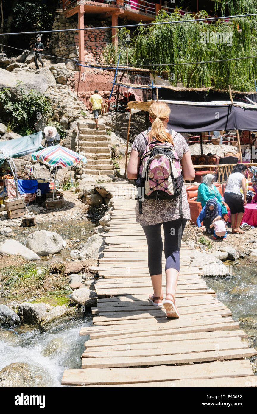 A female tourist crosses over a potentially dangerous rickety bridge over the Ourika River, Ourika Valley, Atlas - Stock Image