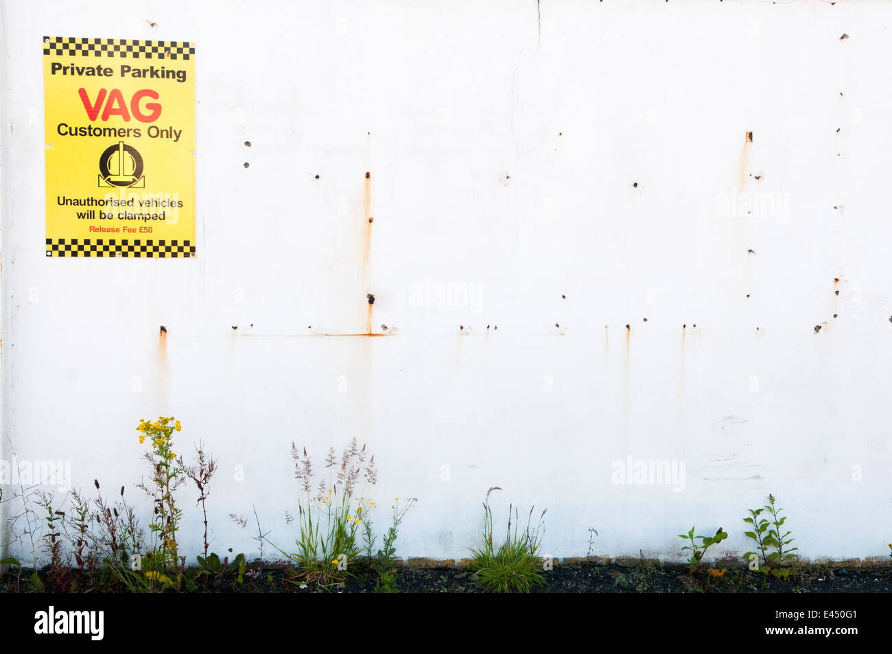 Sign on a wall warning that unauthorised parking will result in vehicles being clamped at a VAG service centre - Stock Image