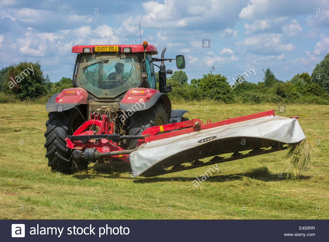 Tractors cutting the grass on Coldhams Common to make hay, ready for the camping site for the Folk Festival - Stock Image