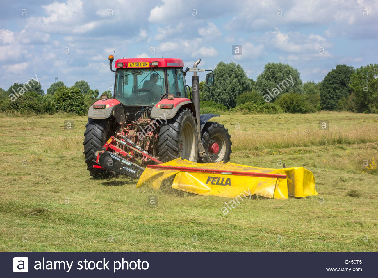 Tractor cutting the grass on Coldhams Common to make hay, ready for the camping site for the Folk Festival - Stock Image
