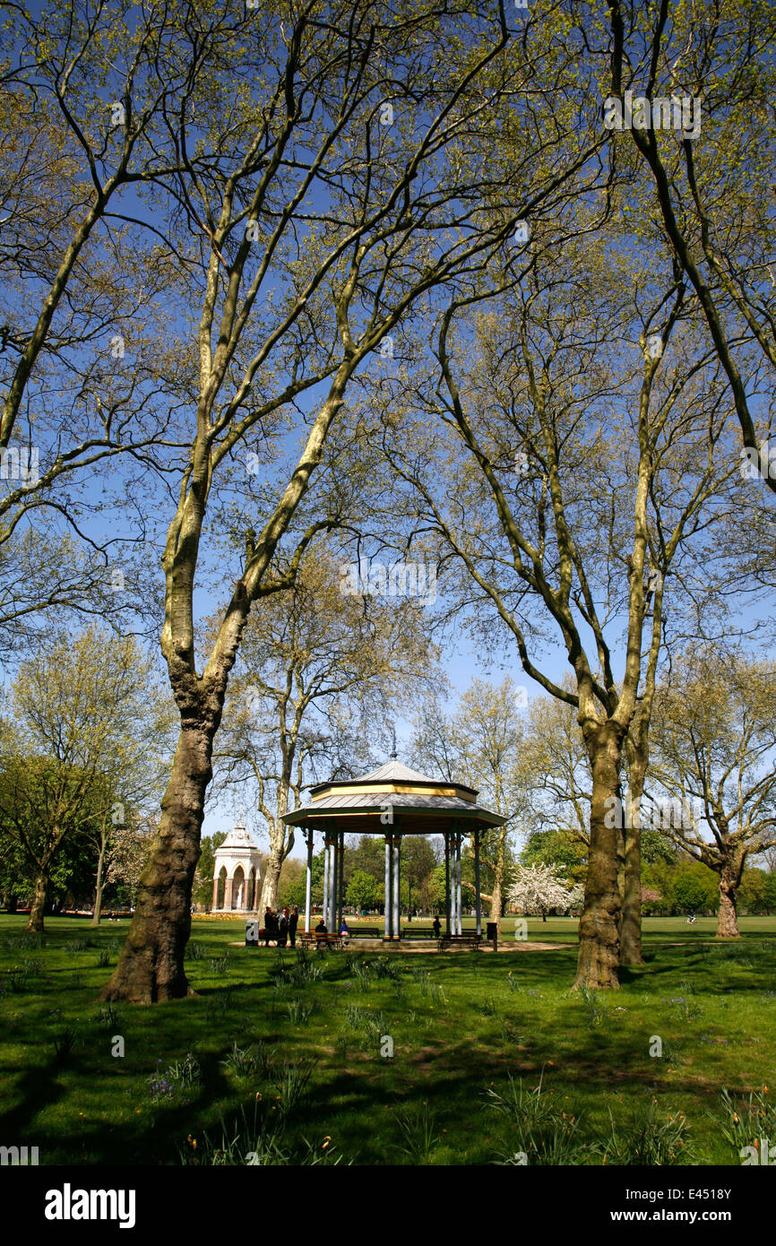 View past the bandstand to the Burdett Coutts Memorial Drinking Fountain in Victoria Park, Hackney, London, UK - Stock Image