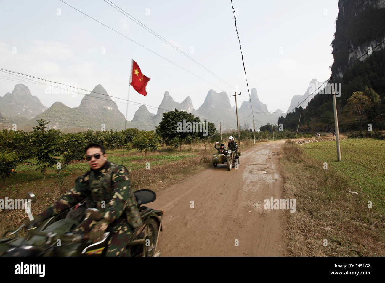Motorcyclist in front of karst mountains in Yangshuo, China Stock Photo
