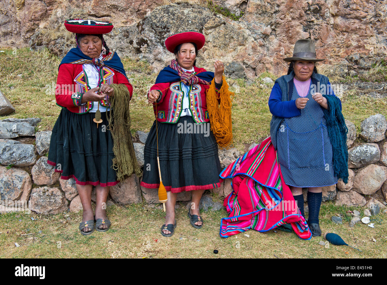 Three elderly women wearing hats, Quechua Indians in traditional dress spinning wool with wooden spindles, Cinchero - Stock Image