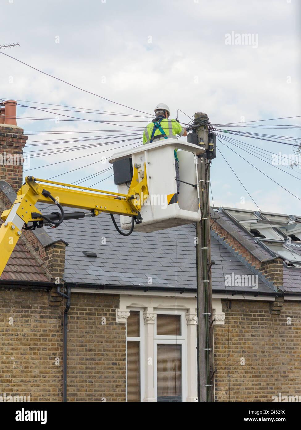 Phone engineer up a telegraph pole, UK - Stock Image