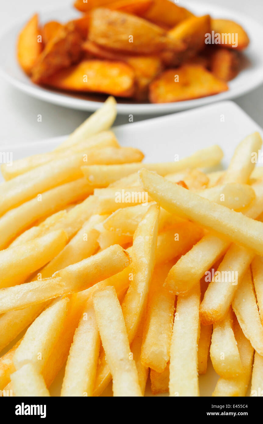 closeup of a plate with french fries and a plate with home fries in the background - Stock Image