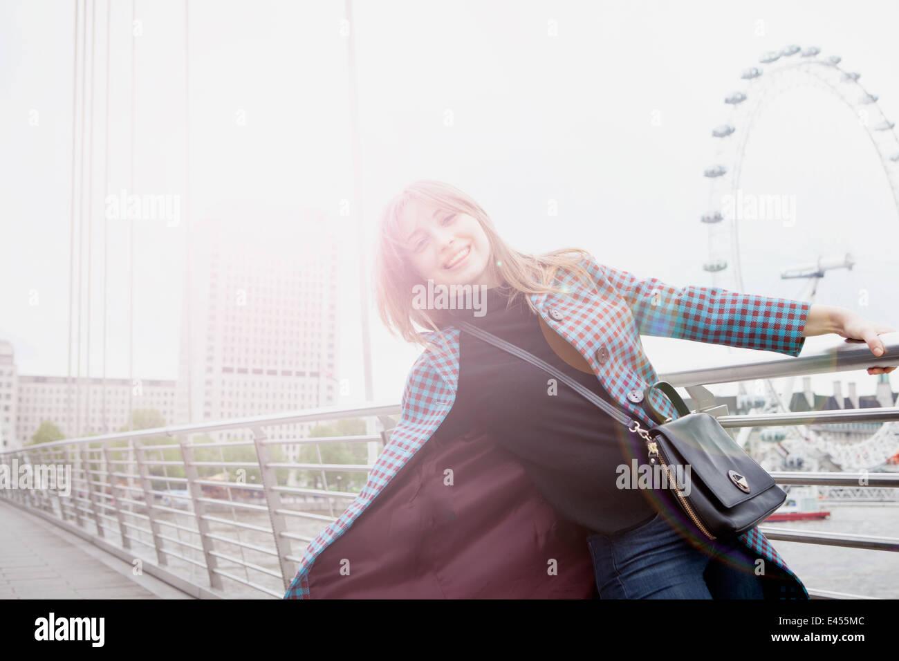 Portrait of young female tourist swinging on Golden Jubilee footbridge, London, UK - Stock Image