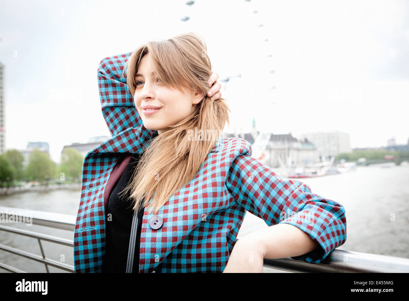 Young female tourist leaning against railings on Golden Jubilee footbridge, London, UK - Stock Image