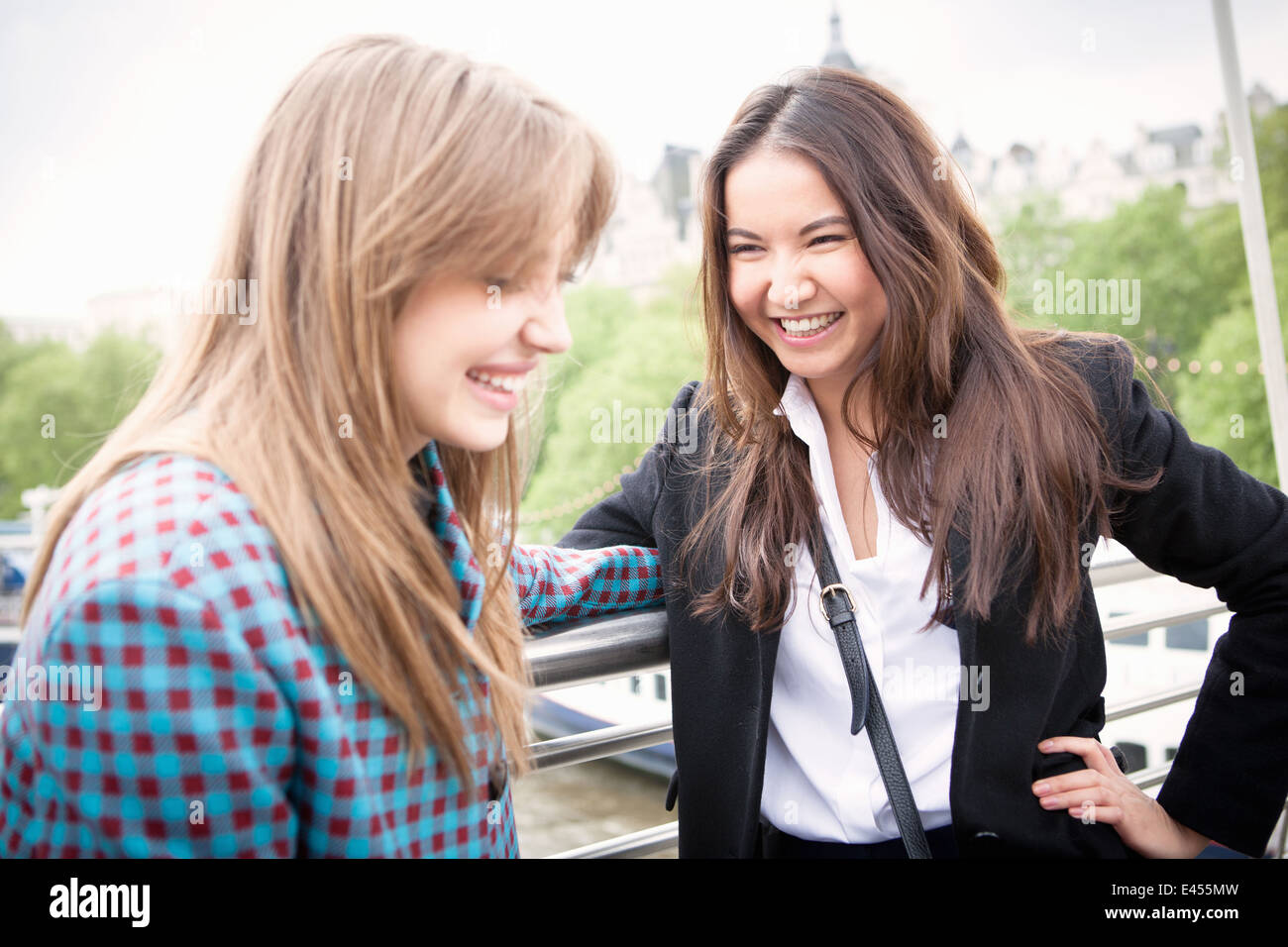 Two young female tourists giggling on Golden Jubilee footbridge, London, UK Stock Photo