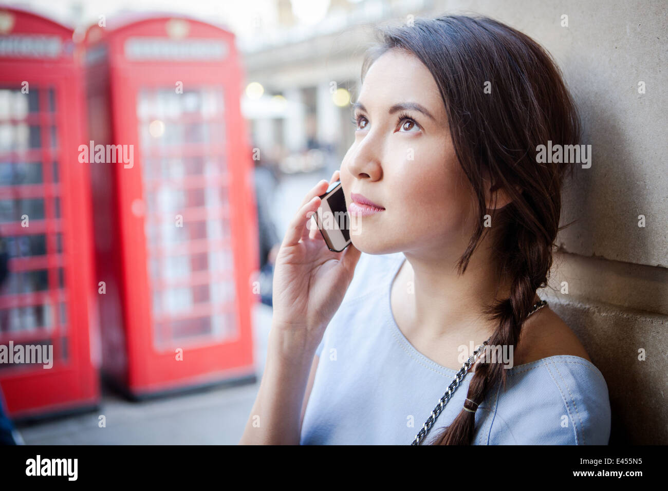 Young woman on smartphone, in front of red London telephone box - Stock Image