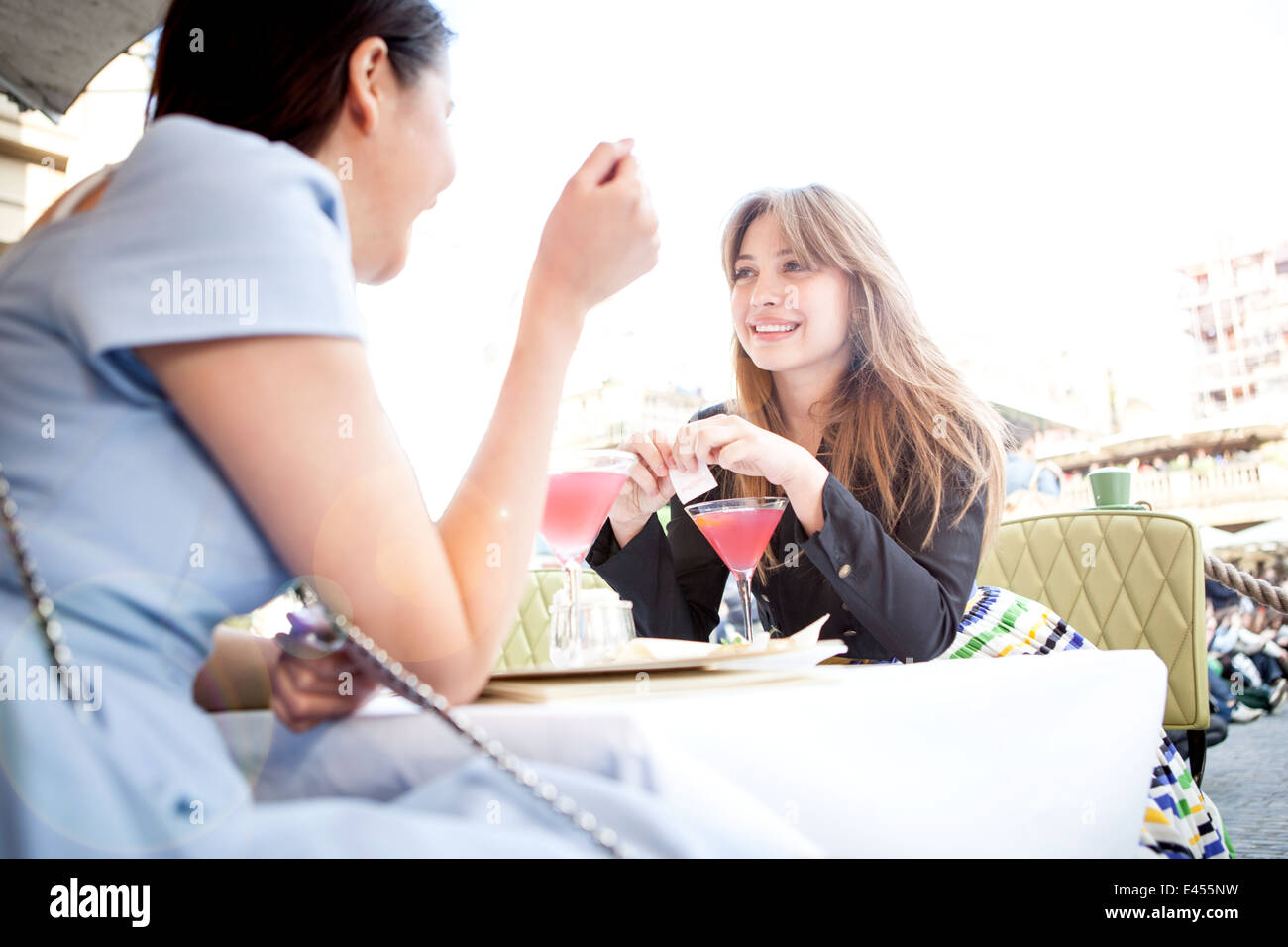Young women sitting at table at outdoor restaurant - Stock Image