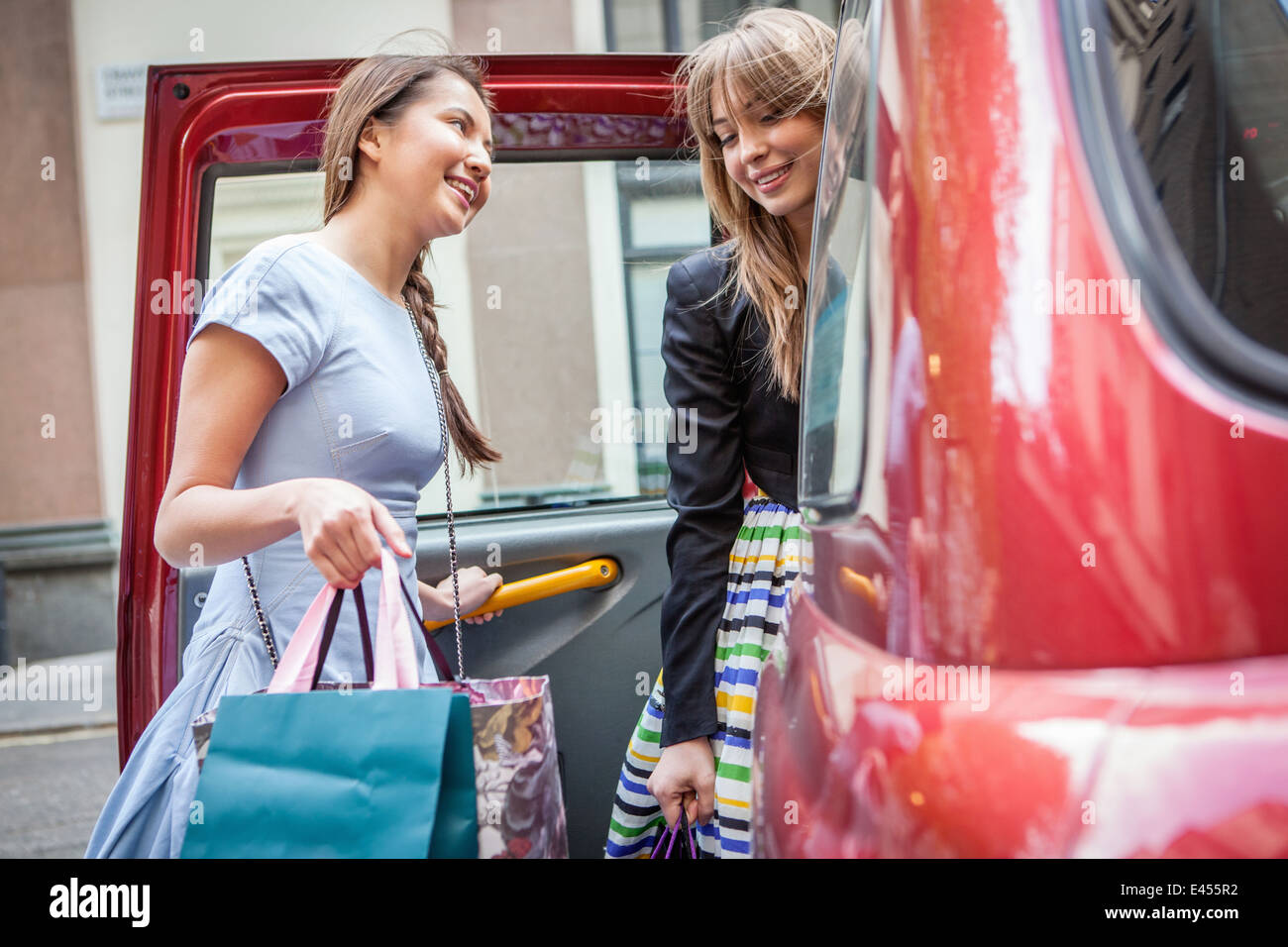 Young women getting into taxicab, carrying shopping bags - Stock Image