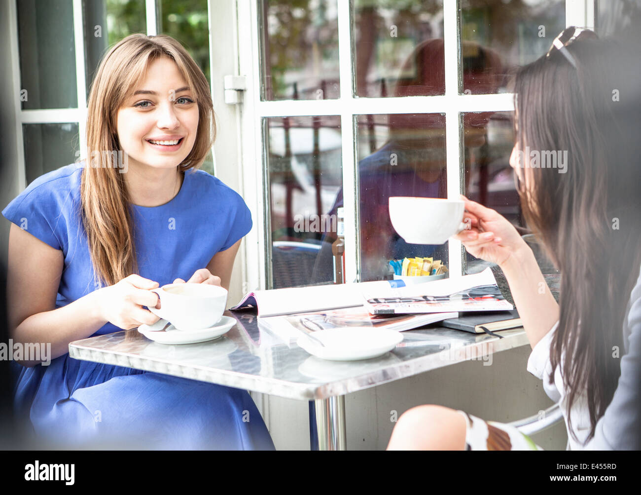 Two young women sitting outside cafe, drinking coffee - Stock Image