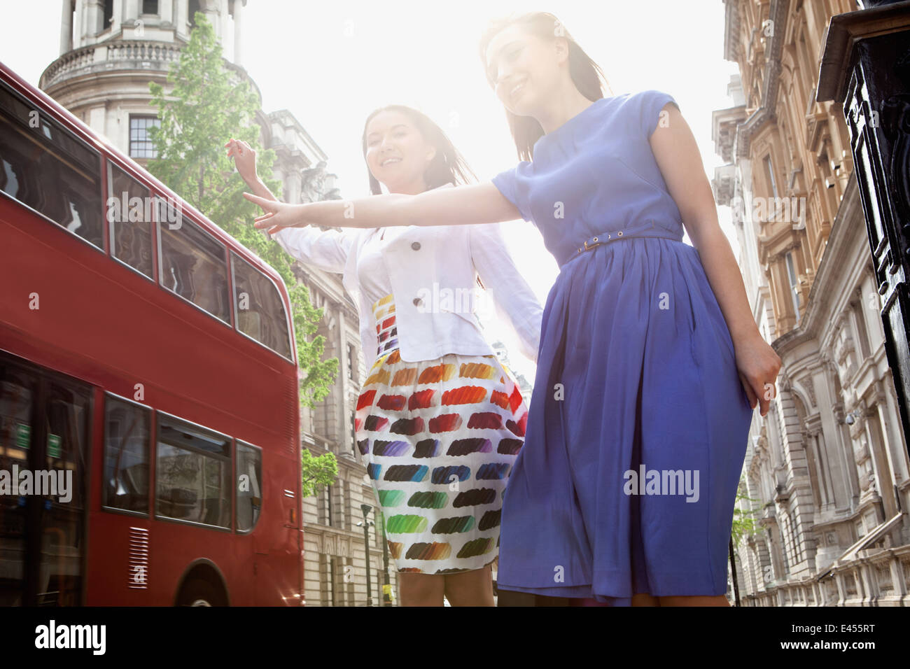 Two young women standing in London street, waving to stop bus - Stock Image