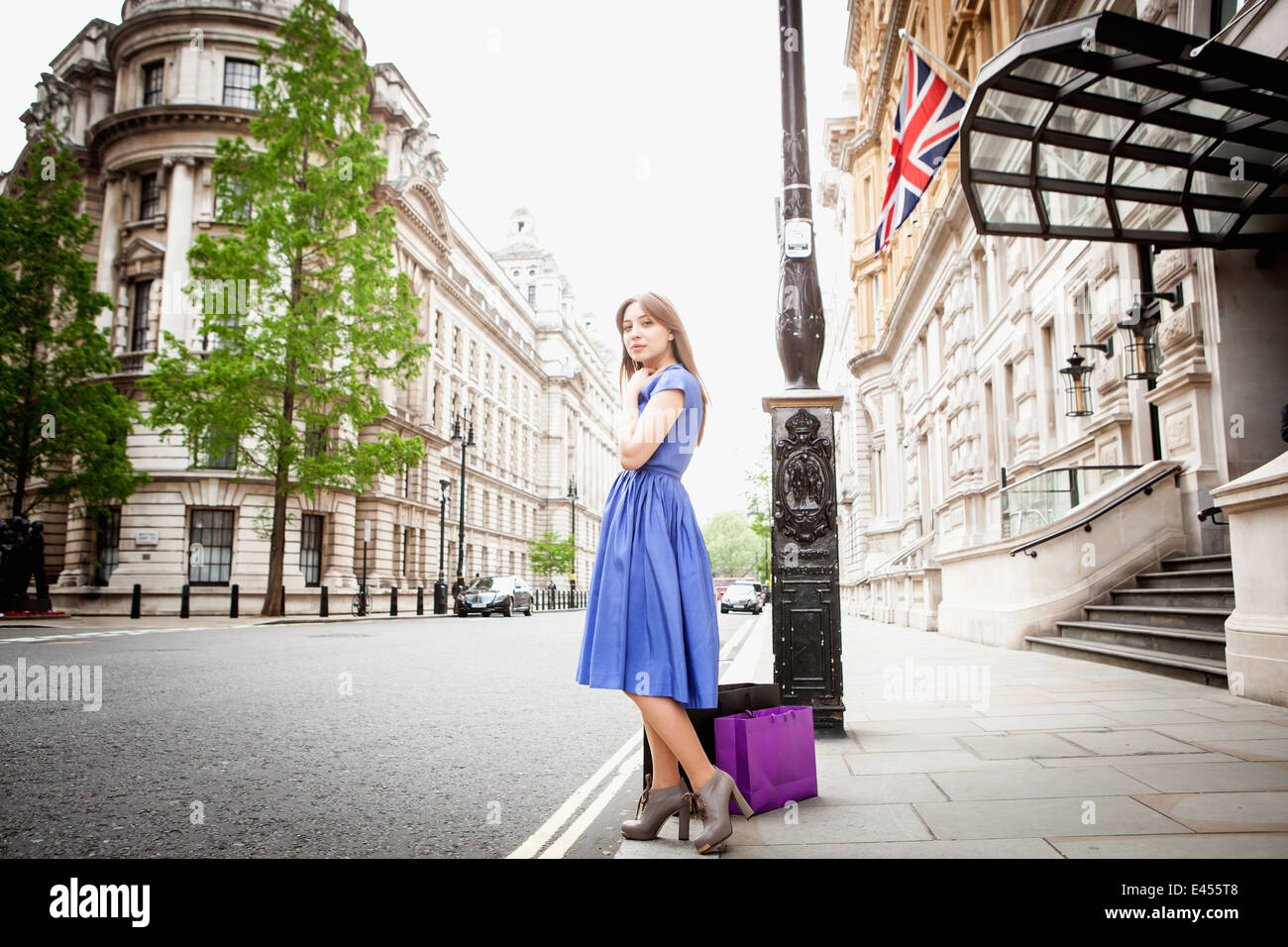 Young woman standing in London street, with shopping bags - Stock Image