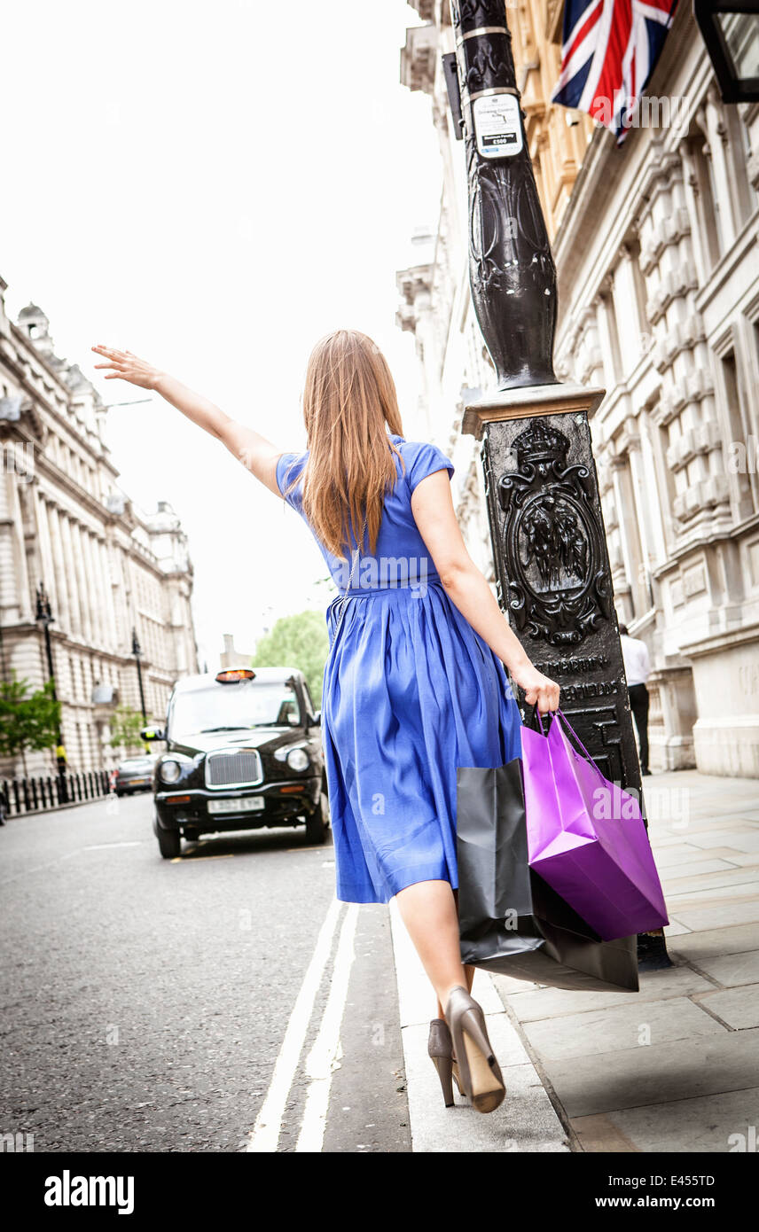 Young woman flagging down London taxi - Stock Image