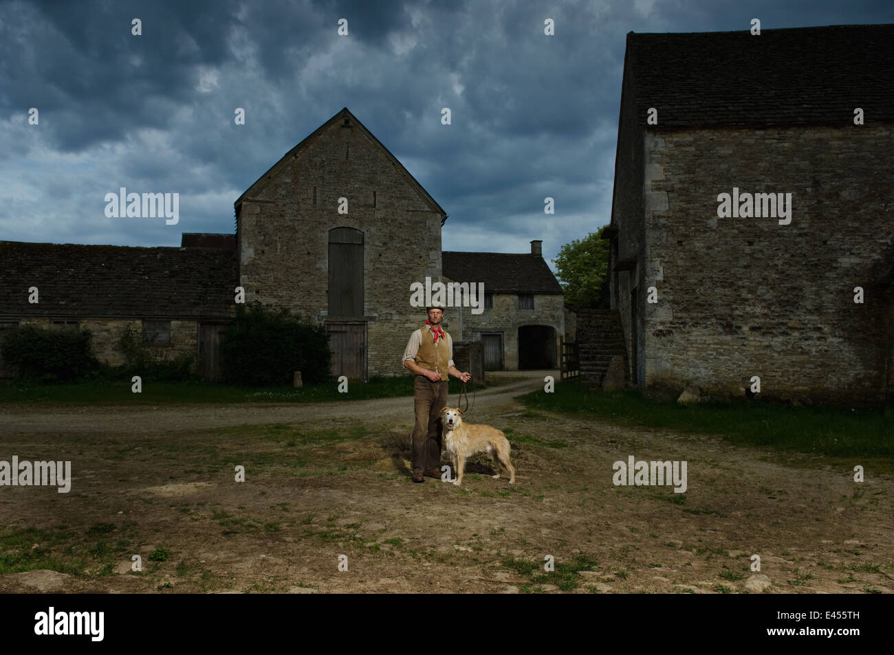 Portrait of mature traditional farmer and his lurcher dog in farmyard - Stock Image