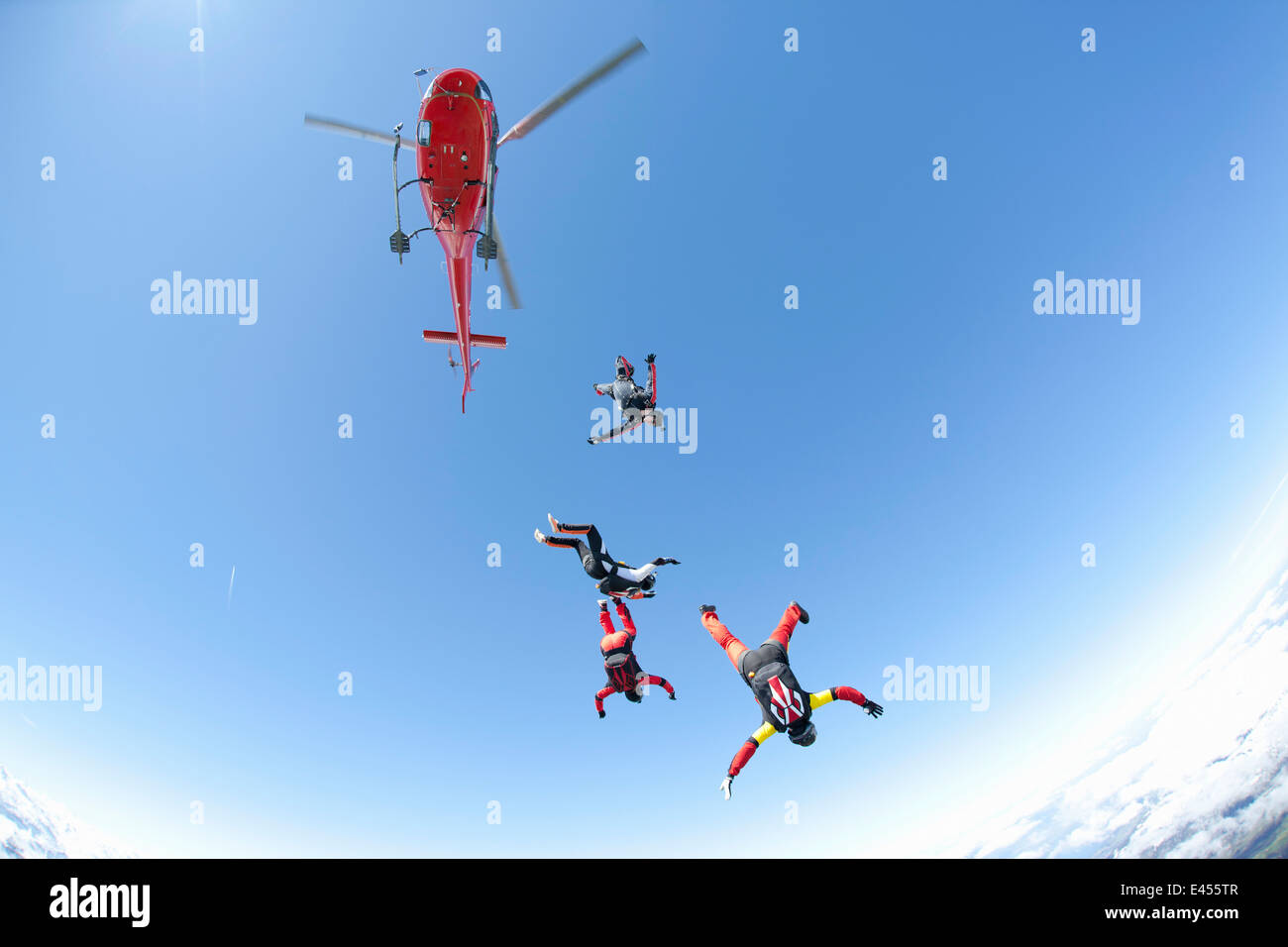 Skydiving team of four free falling from helicopter - Stock Image