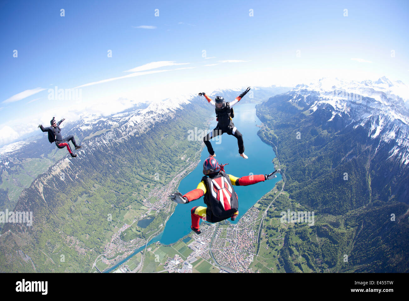 Team of three skydivers in formation over Interlaken, Berne, Switzerland - Stock Image
