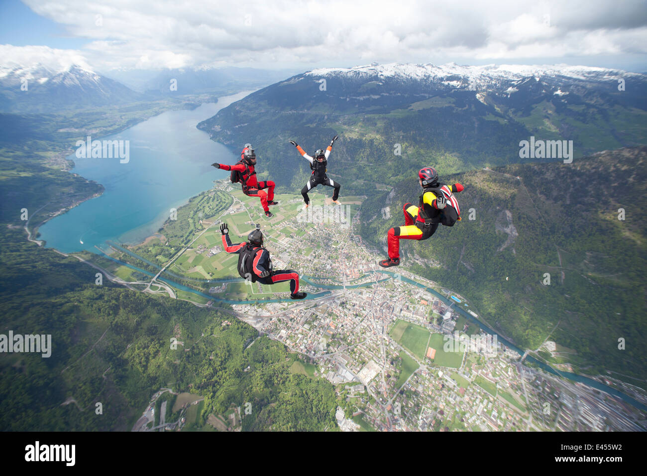 Team of four skydivers in formation over Interlaken, Berne, Switzerland - Stock Image