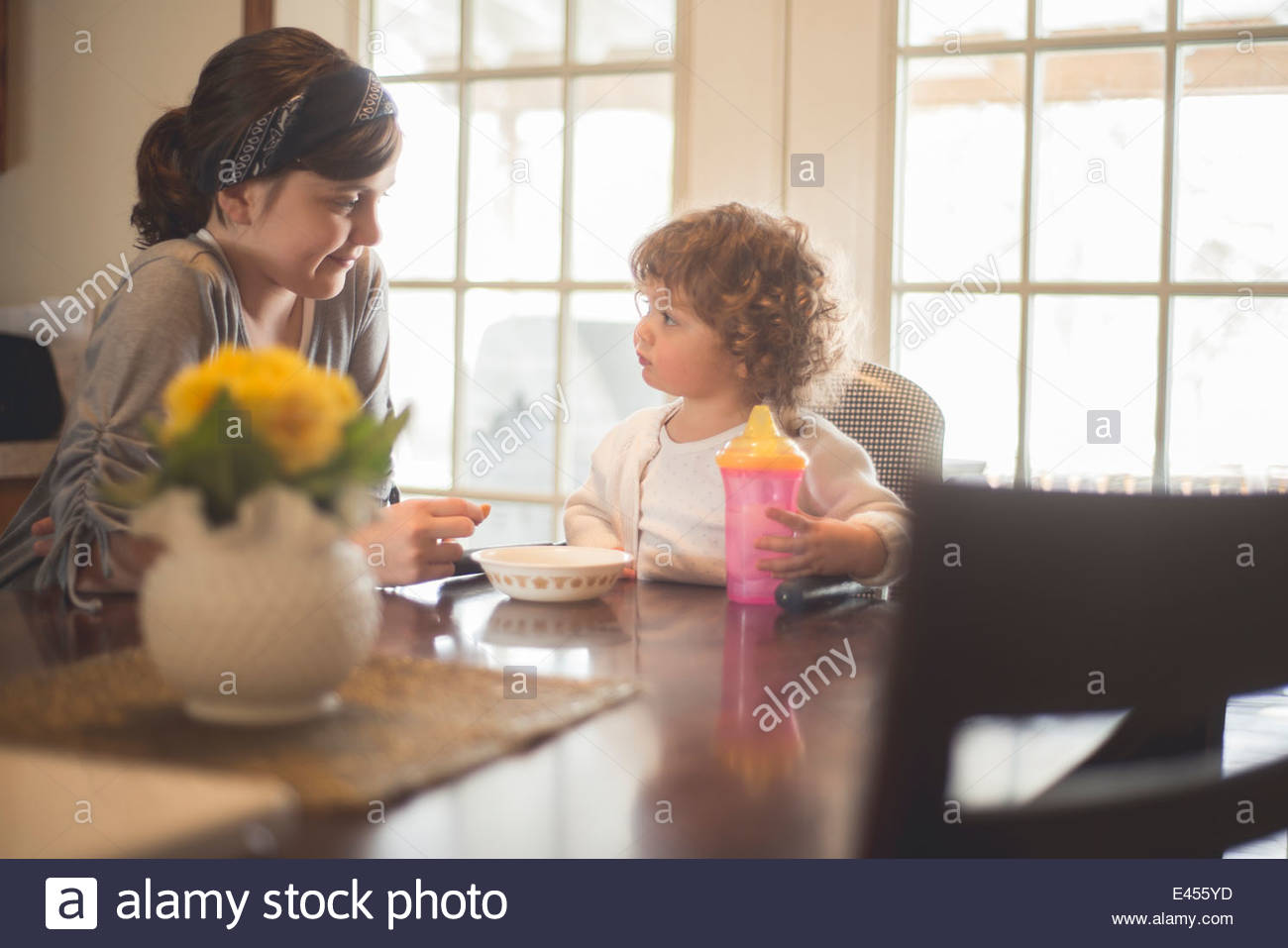 Older sister sitting at breakfast table with younger sister - Stock Image