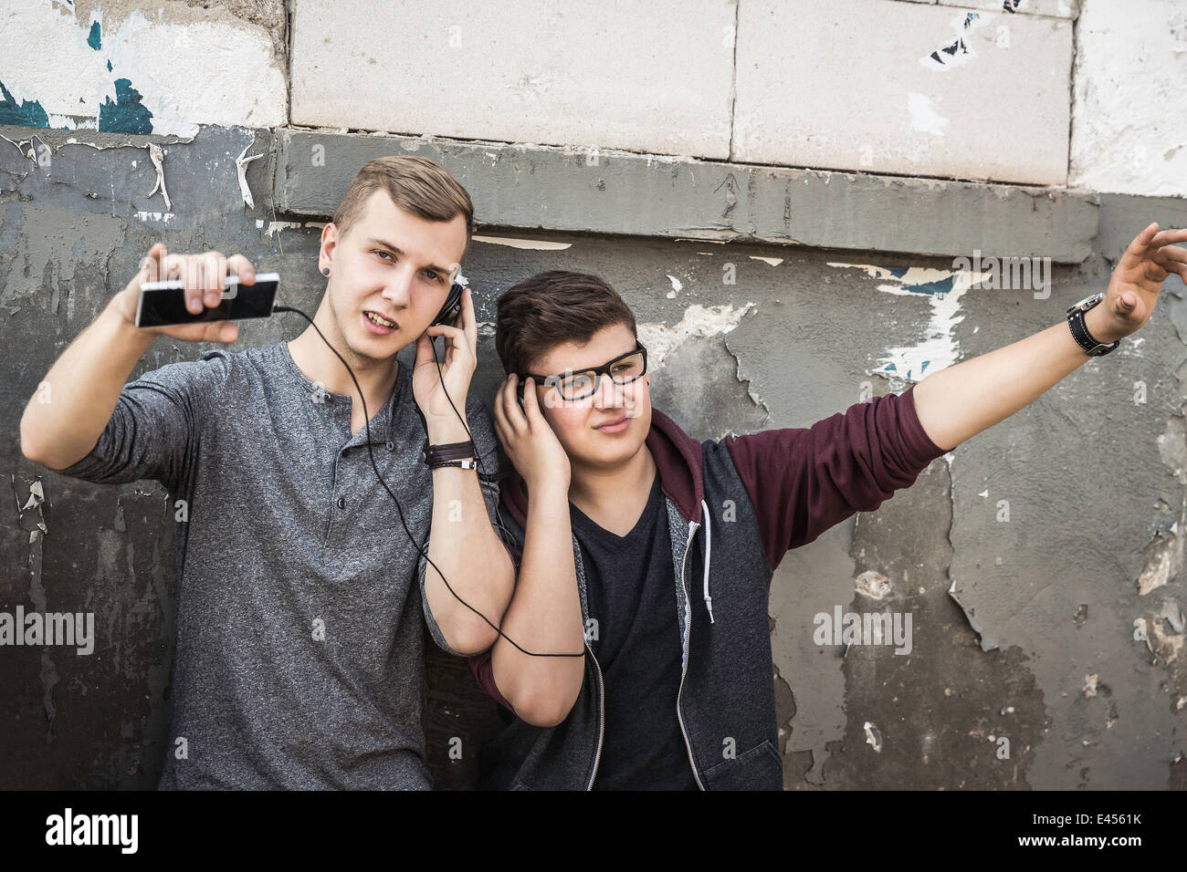 Teenage boys listening to music by abandoned building - Stock Image