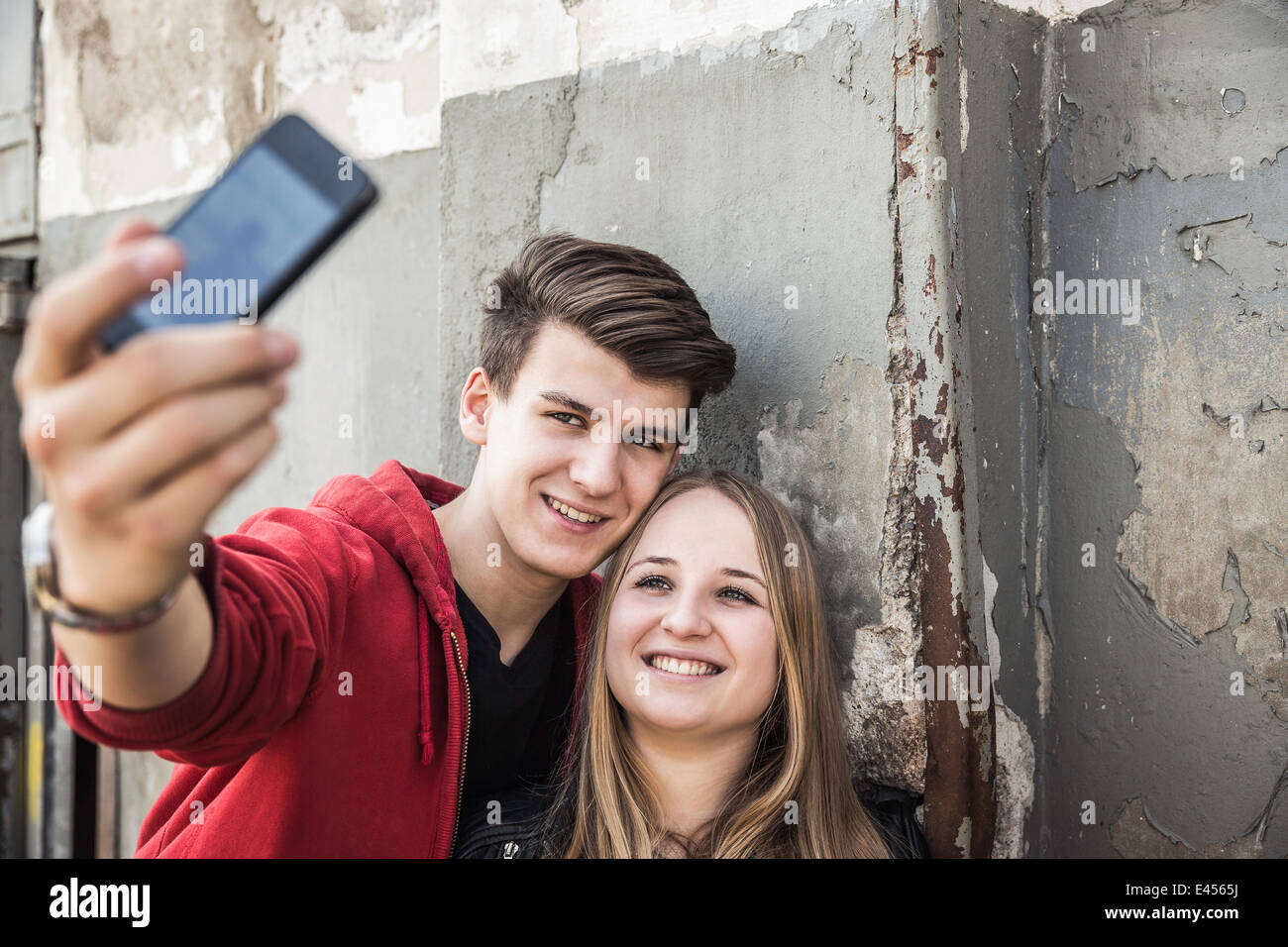 Teenage couple taking selfie by abandoned building - Stock Image