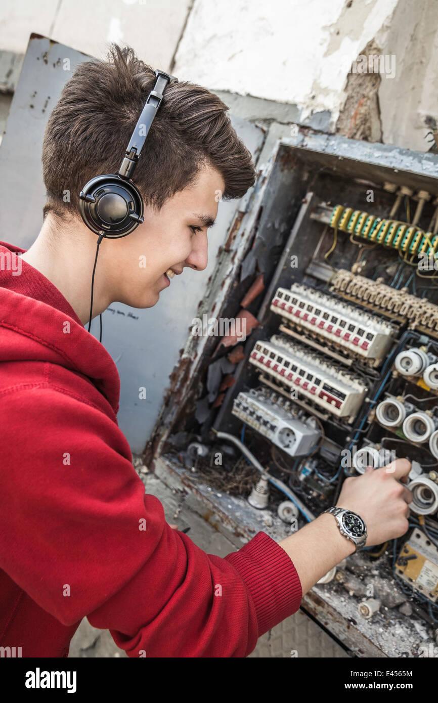 Teenage boy using electrical fuse box like DJ console - Stock Image