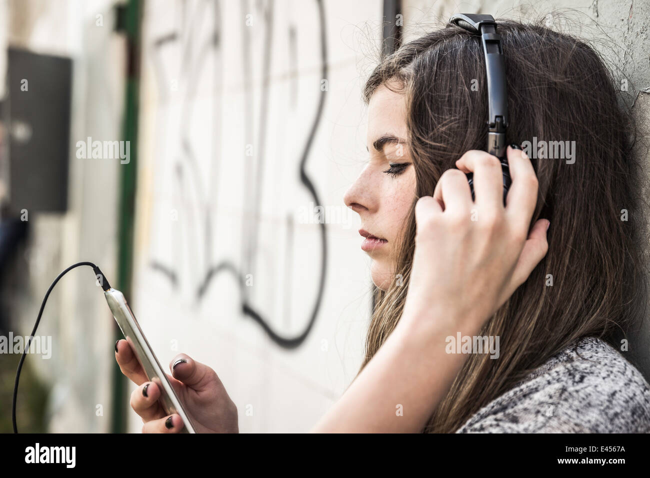 Girl listening to music on smartphone - Stock Image