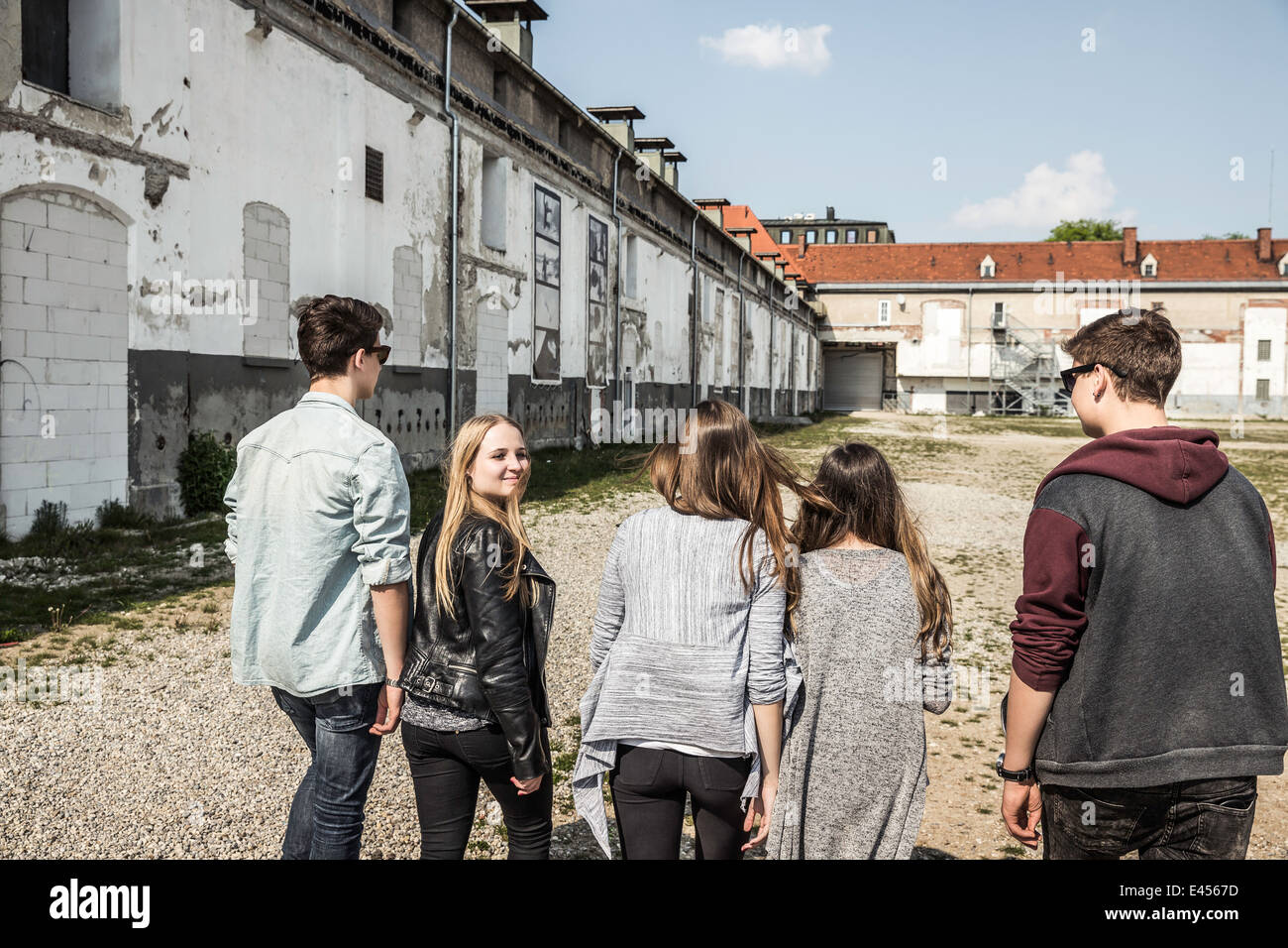 Teenagers strolling past abandoned buildings - Stock Image