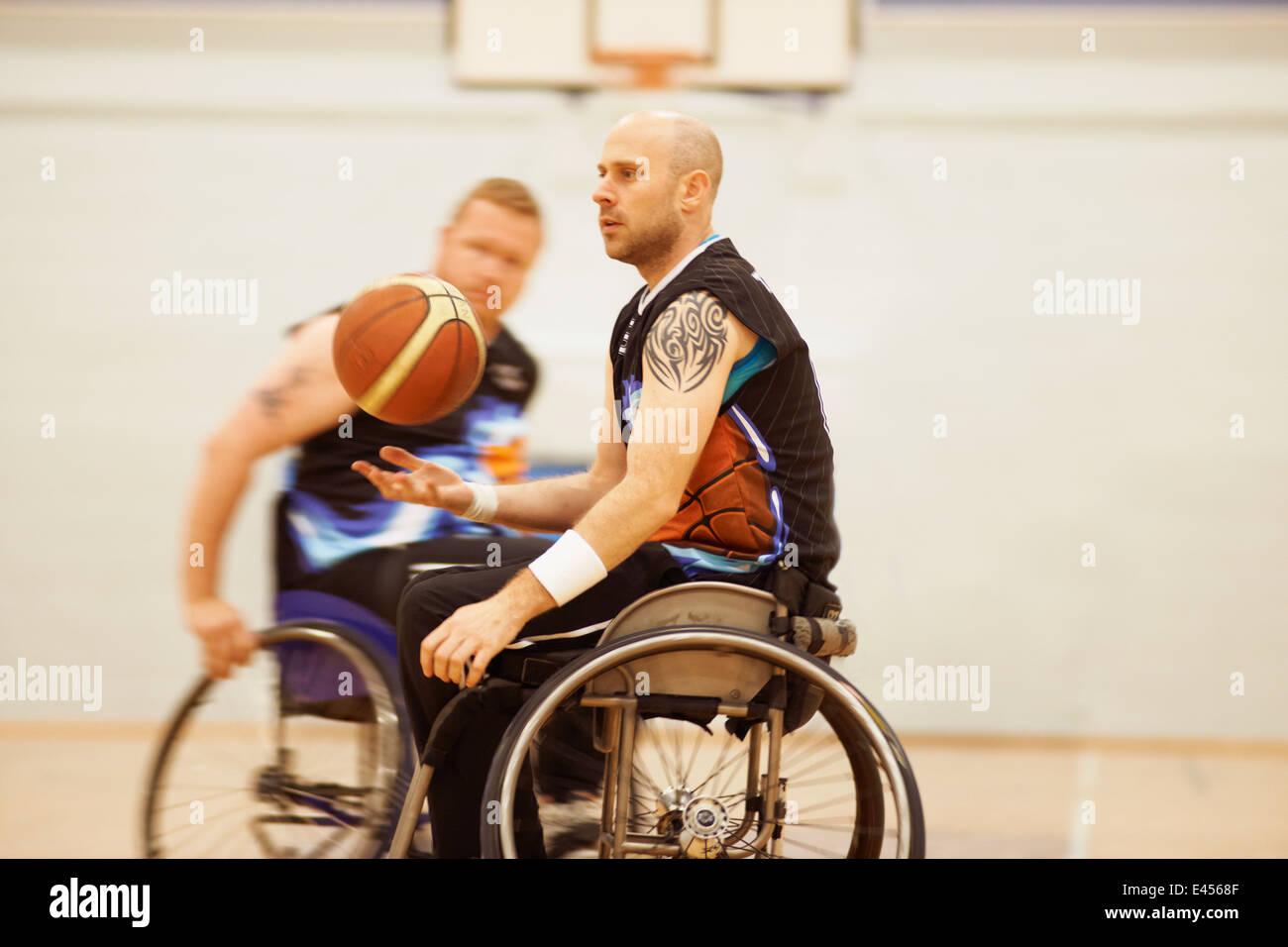 Wheelchair basketball player bouncing ball - Stock Image