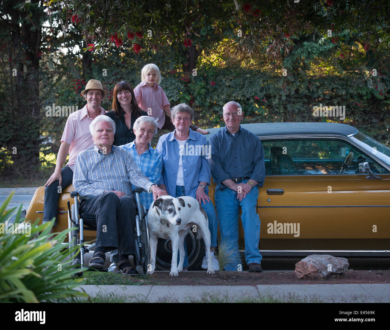 Three generation family portrait with dog - Stock Image
