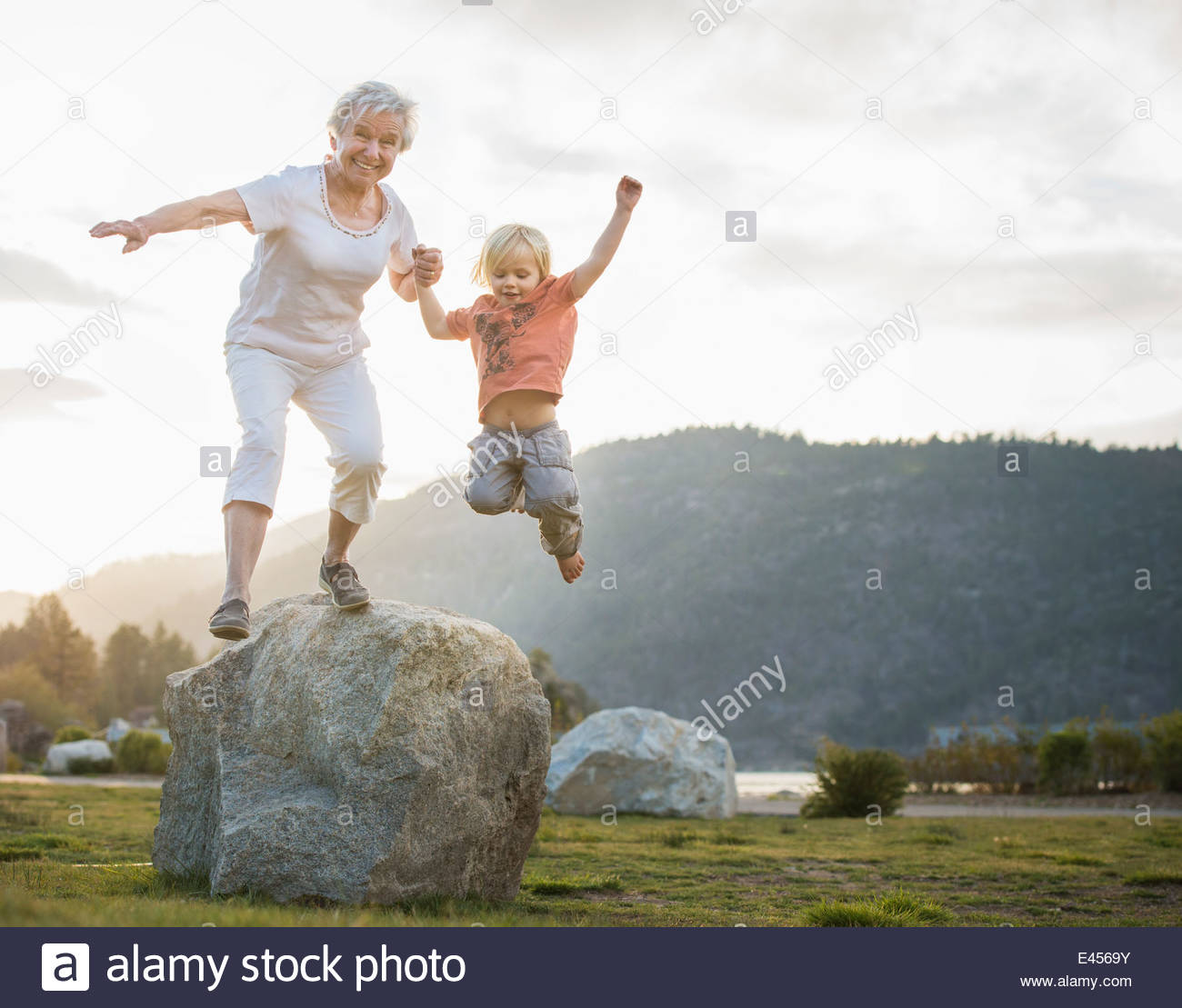 Senior woman and grandson jumping mid air, Big Bear Lake, California, USA - Stock Image