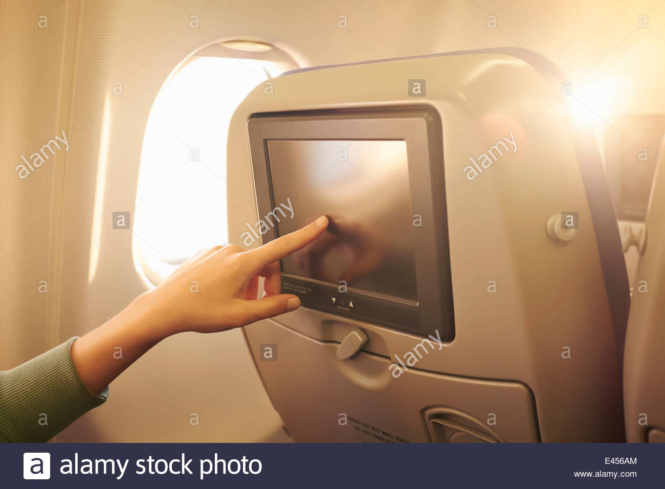 Close up of female hand using touchscreen in airplane headrest - Stock Image