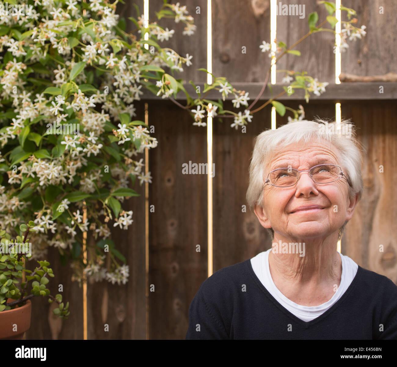 Portrait of smiling senior woman in garden gazing upward - Stock Image