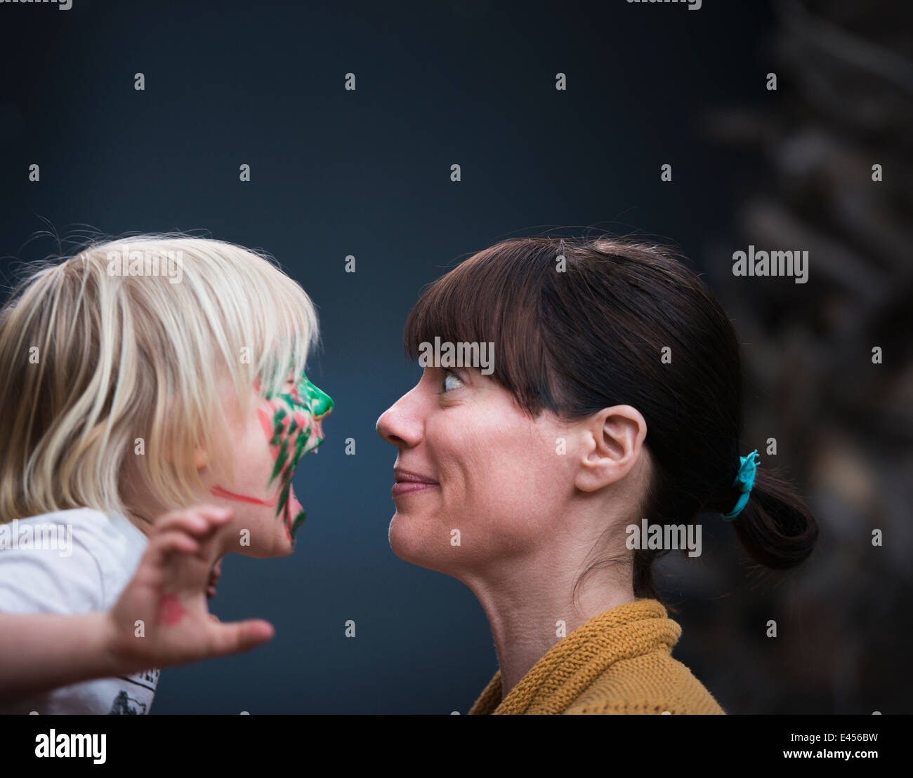 Face to face portrait of mothers surprise at young sons painted face - Stock Image